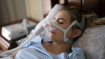 A woman wears a CPAP mask for sleep apnea