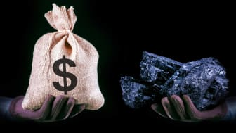 person holding money bag and coal