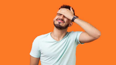 picture of a man smacking his forehead because he forgot to file his taxes