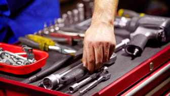 Cropped image of a man's hands grabbing a tool from his toolbox