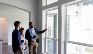 Confident male real estate agent gestures toward a beautiful view out the window of a new home. Interested potential homeowners attentively listen to the real estate agent.