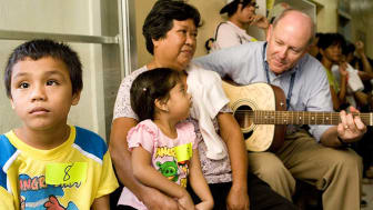 Dyson plays his guitar for children as they wait to be seen.