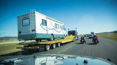 Recreational vehicle loaded onto a semi-trailer being taken to a shop for repairs