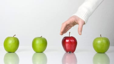 Out of four apples, three are green and one is red. A hand reaches for the red one.