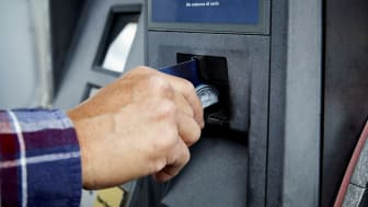 Man putting credit card in gas pump ATM to pay for gas at a gas station