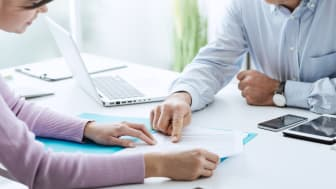 Young woman having a business meeting with an executive in his office, he is pointing on a contract and giving explanations