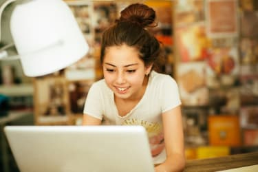 Smiling pre-teen working with laptop