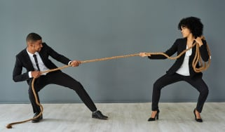 A man and a women in business suits fight in a tug of war battle.