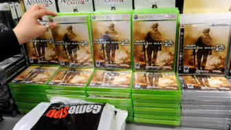 """LAS VEGAS - NOVEMBER 10:GameStop worker Cami Terada sells copies of the highly anticipated video game """"Call of Duty: Modern Warfare 2"""" at a GameStop Corp. store early November 10, 2009 in Las"""