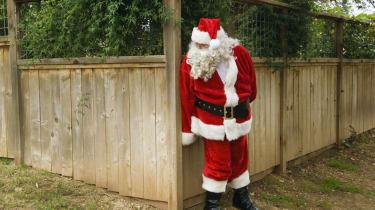 Santa hiding behind fence
