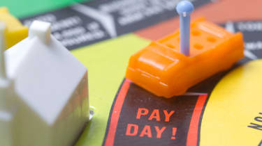 """A board game with a toy car reaching the """"Pay Day"""" spot."""
