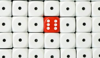 Stacks of white dice showing a single dot surround one red die with a six on it.