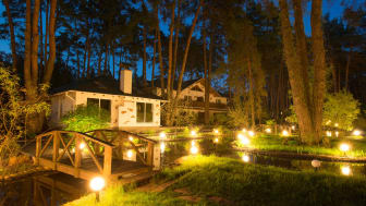 A home at night in a forest with unique exterior lighting