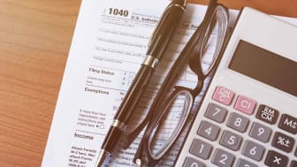 picture of income tax form, calculator, pen and a pair of glasses