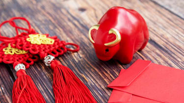 A Chinese New Year display of a red ceramic ox, red tassels and red envelops.
