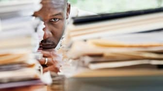 A man peeks out from behind a pile of documents.