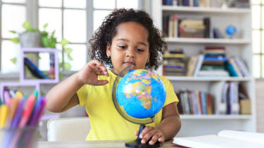Little girl pointing at globe
