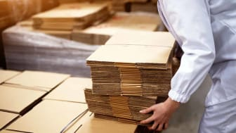 Close up of young female worker picking up stacks of folded cardboard boxes from a bigger stack in factory storage room.