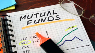 """A highlight sits on top of a notebook with the words """"mutual funds"""" written on it."""