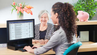 Senior woman working with a teller in a bank