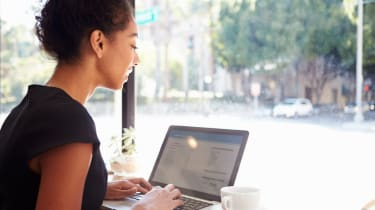 Businesswoman Working Using Laptop In Coffee Shop