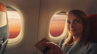 Woman in airplane paying contactless with credit card ++++ Note for the inspector: Credit card is fake and made especially for the photosession ++++