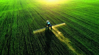 tractor spraying fertilizer on crops