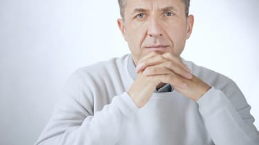Portrait of middle aged serious businessman sitting with hands
