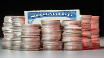 picture of a Social Security card surrounded by stacks of coins