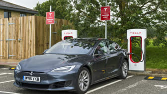 Abington, Scotland, UK - August 7, 2016: A Tesla electric car parked at a Tesla super charger charging station in the car park of Abington services in Lanarkshire, Scotland. The car is plugge