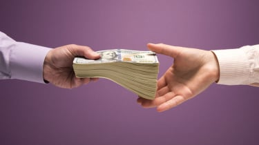 One man and one woman's hands handing off large stack of US 100 bills, purple background