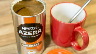 Poole, UK - April 1, 2016: A ton of Azera instant coffee from maker Nescafe with a mug and spoon. Barista Style Instant Coffee - Americano.