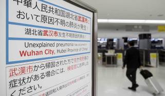 NARITA, JAPAN - JANUARY 17: A passenger walks past a notice forpassengers from Wuhan, China displayed near a quarantine station at Narita airport on January 17, 2020 in Narita, Japan. Japan's