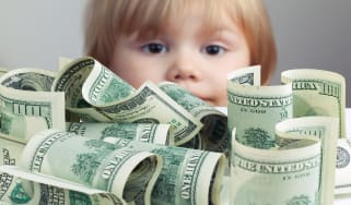 picture of one hundred dollar bills on a table with a young child peering over it in the background