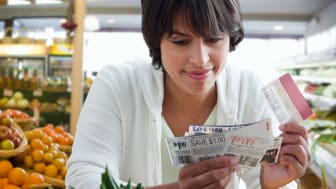 A woman shopper looks over her coupons inside a supermarket