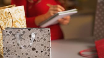 Closeup on christmas shopping bag and woman checking list of presents in background