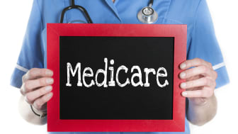 """picture of doctor holding sign that says """"Medicare"""""""