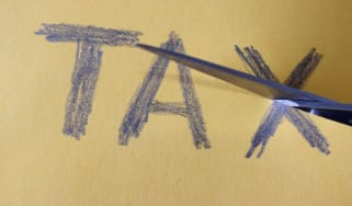 """picture of scissors cutting paper with """"tax"""" written on it"""