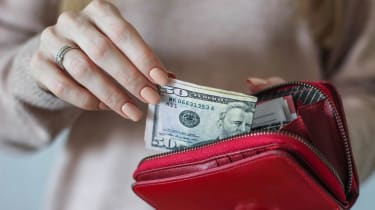 A woman pulls money out of a red wallet.