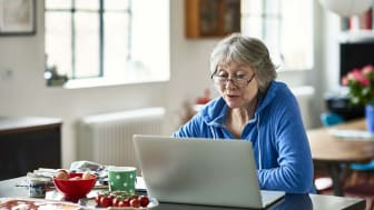 Caucasian woman in her 50s concentrating, peering at screen, working on home finances, planning for retirement