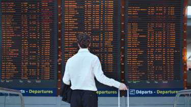 passenger looking at timetable board at the airport