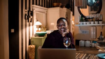 A smiling woman having a glass of wine while looking at her laptop