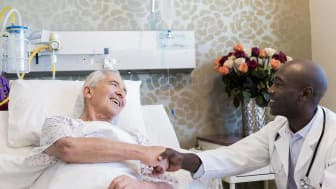 Smiling doctor shaking hands with senior patient. Practitioner sitting by man lying on bed. Multi-ethnic males are in hospital ward.