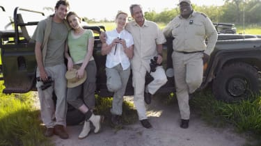Two couples and ranger by jeep, smiling, portrait