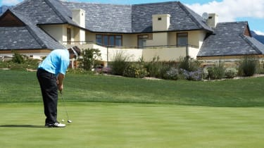 Golfer putting on a golf course with large homes nearby