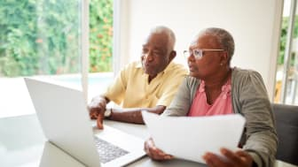 Senior couple with a paper looking at a laptop at home