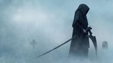 Grim Reaper in a fog-covered cemetery