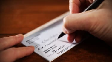 Writing a donation check to a charitable organization