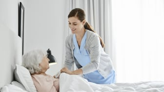 A nurse helps a nursing home resident get tucked into bed.