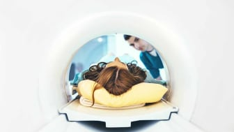 Unrecognizable female patient entering a mri scan while technician standing and looking at her.